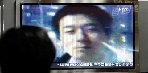 En kvinna i Sydkorea ser Robert Park på en tv-skärm under en nyhetssändning.