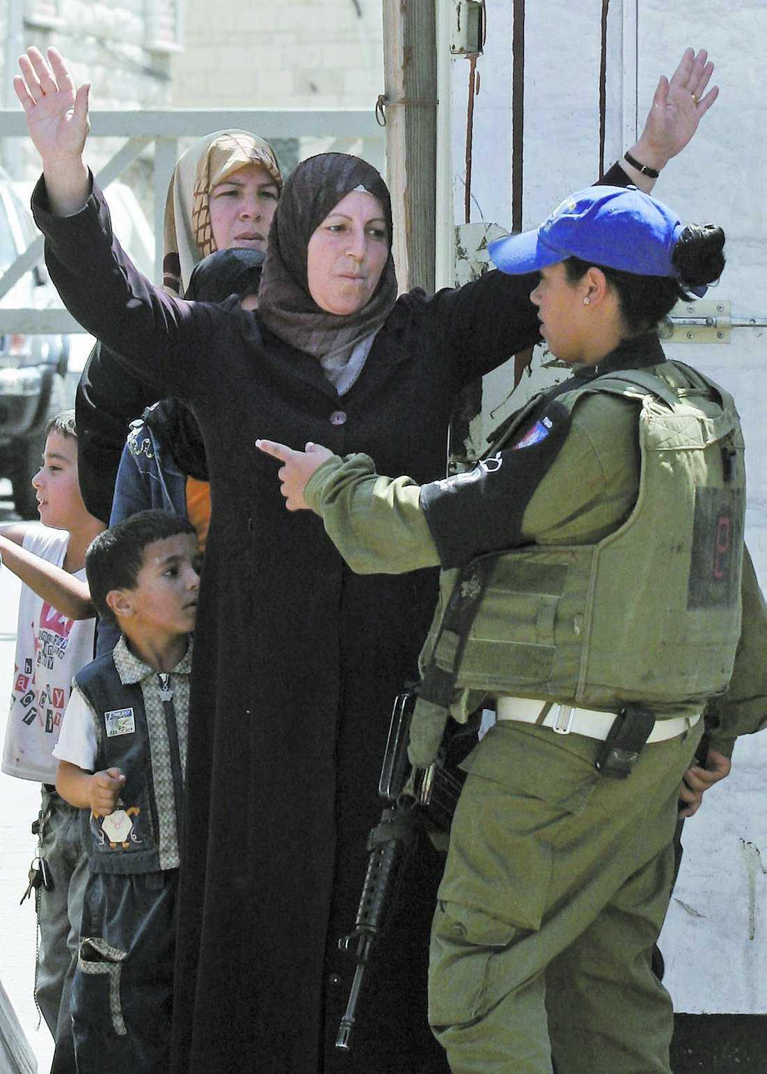En palestinsk kvinna visiteras av en israelisk soldat i Hebron på Västbanken.