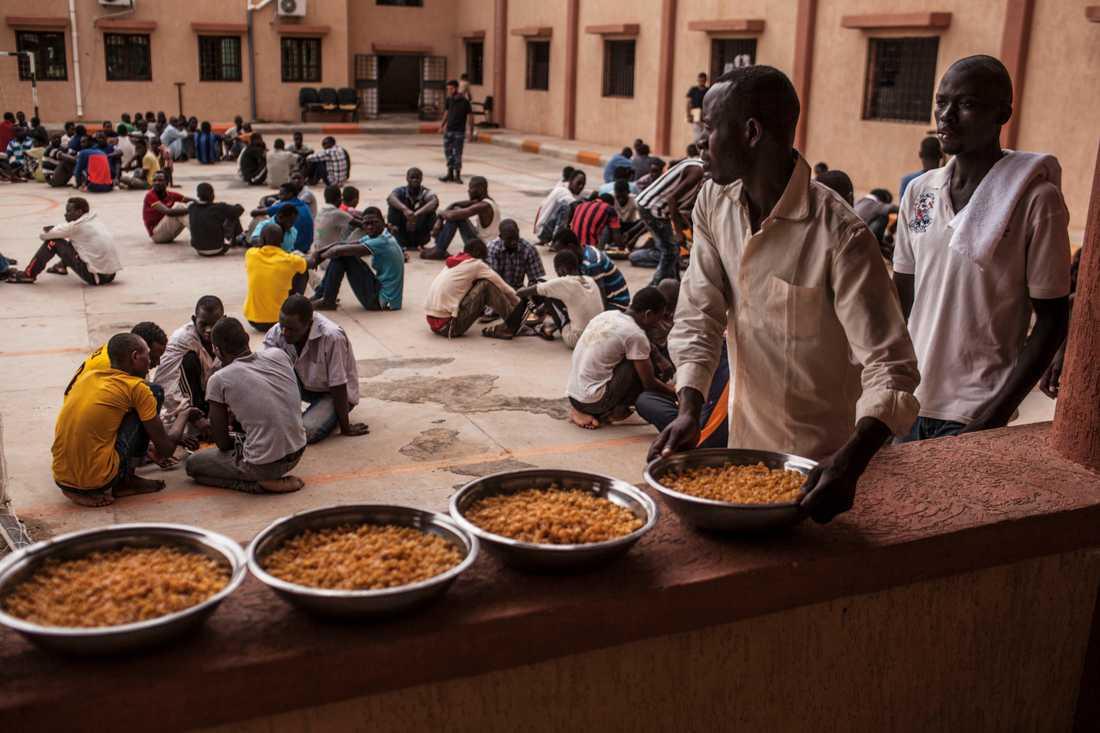 Arkivbild. En migrant håller en skål med pasta under en lunch i ett flyktingförvar i Libyen.