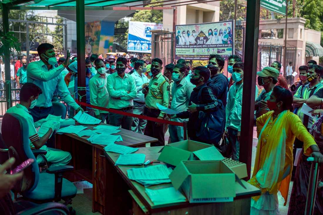 En otålig folkmassa – där få håller avstånd – väntar på att registrera sig för att ta covidprov på ett sjukhus utanför New Delhi i Indien.