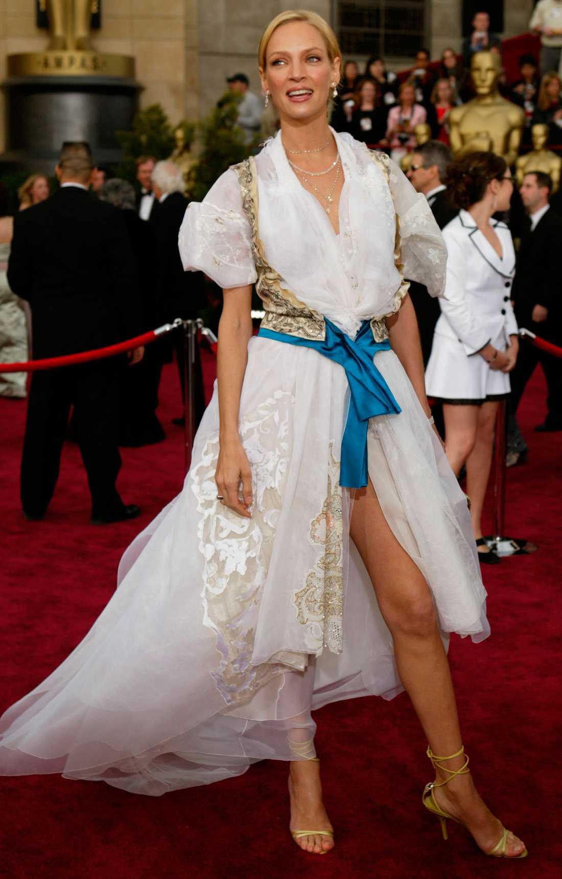 """Uma Thurman 2004 """"Var det en galaklänning eller hade hon helt enkelt bara försovit sig och sprungit hit i sina sänglakan? Ja, ingen visste riktigt och kanske visste inte ens designern Christian Lacroix? Allra minst visste nog Uma själv, men hon gjorde sitt bästa för att inte se bekymrad ut."""""""