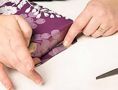 3. Vik kortsidorna på paketet. Har du för mycket papper, börja vik sidorna inåt och klipp bort överskottet. Vik in kanterna på sidoflikarna för ett mjukt resultat och fäst med dubbelhäftande tejp.
