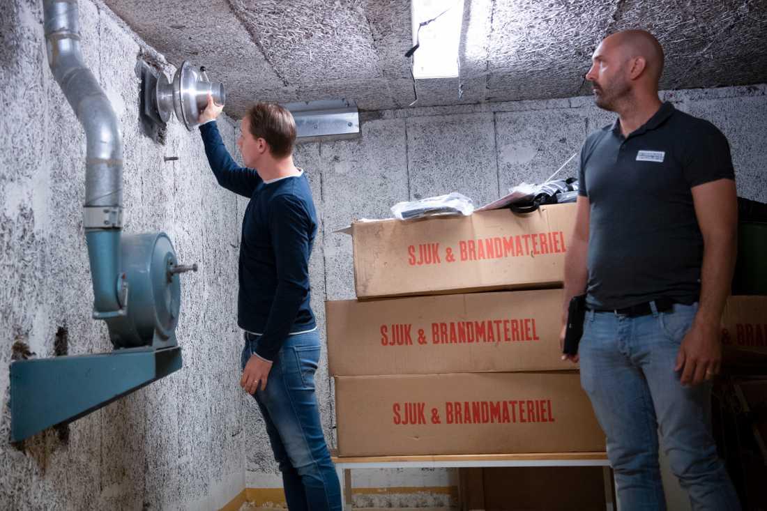 Richard Malm, skyddsrumssakkunnig, visar hur en stötvåg kan stoppas i ett skyddsrum. Patric Forsberg står intill.