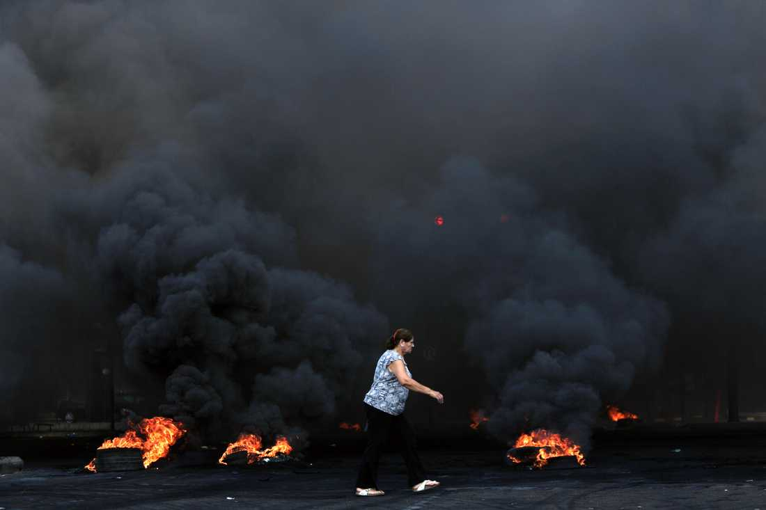En kvinna går förbi brinnande bildäck under protesterna i Beirut.