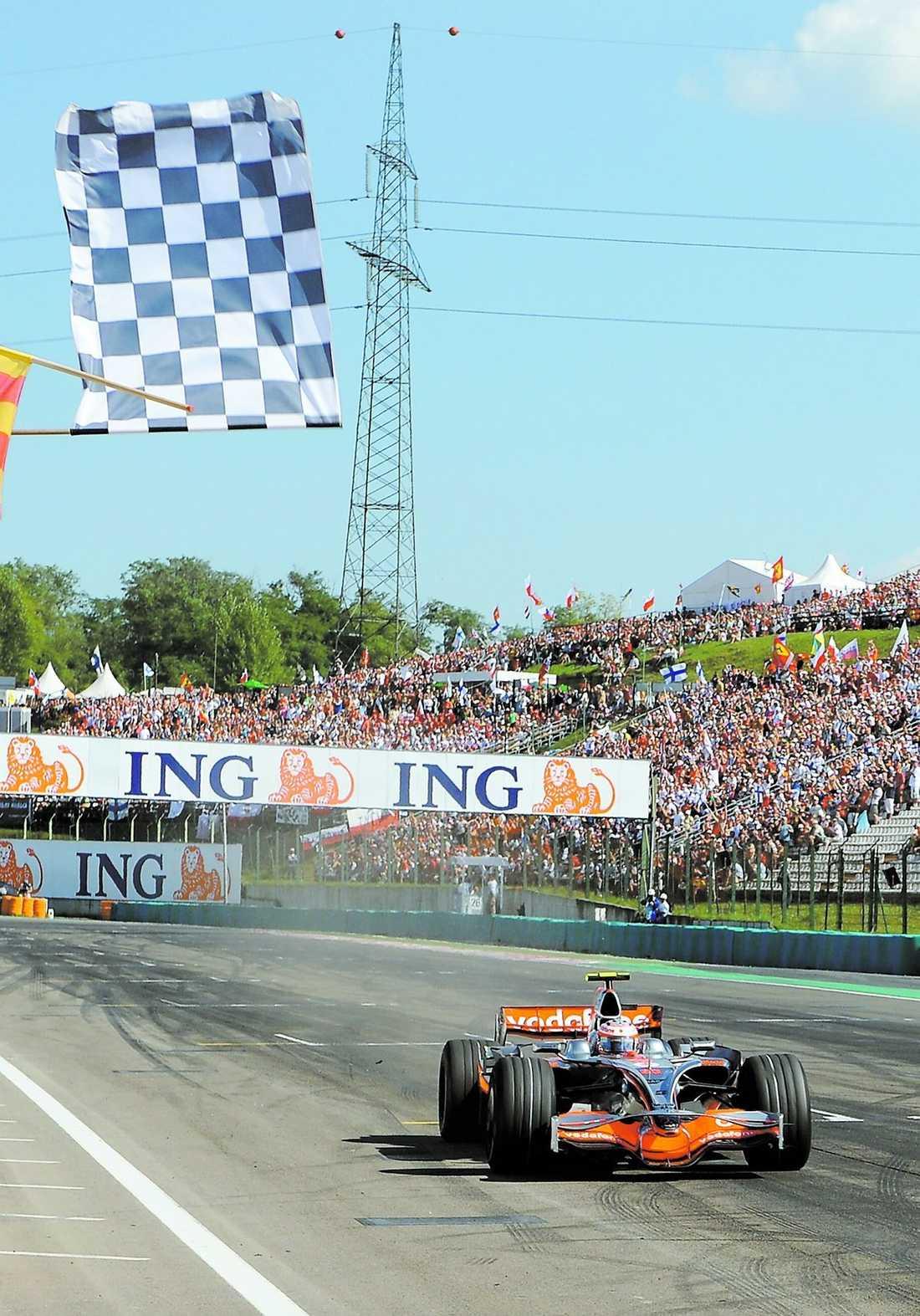 FÖRSTA SEGERN Heikki Kovalainen korsar mållinjen i Ungerns GP-lopp. Det var den 26-årige finländarens första seger i sitt 28:e F1-race.