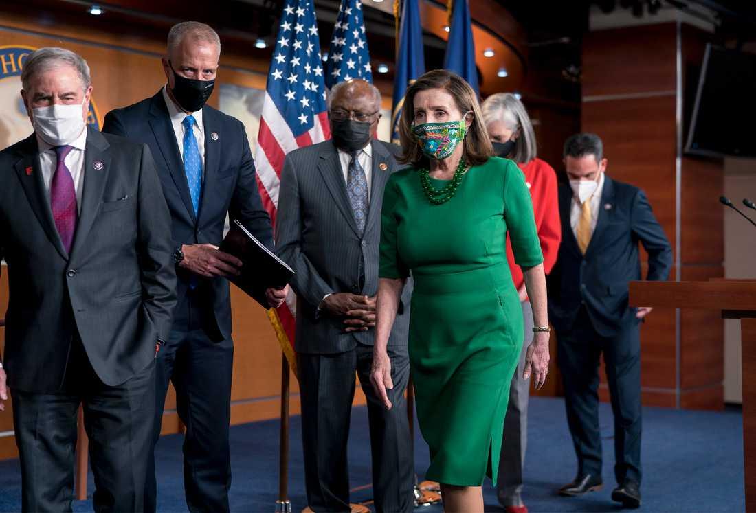 Representanthusets demokratiska talman Nancy Pelosi, i grönt, omgiven av partikamrater kort före omröstningen om hjälppaketet.