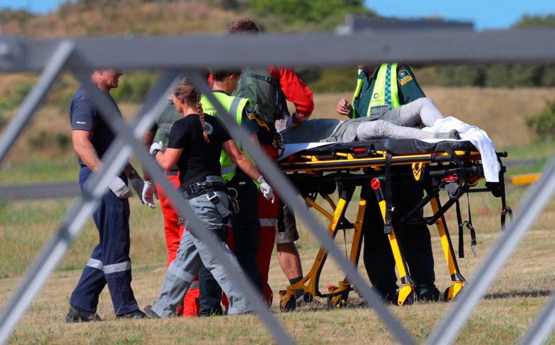 Räddningspersonal tar hand om en skadad person som anlänt till Whakatane flygfält efter vulkanutbrottet på White Island, Nya Zeeland.