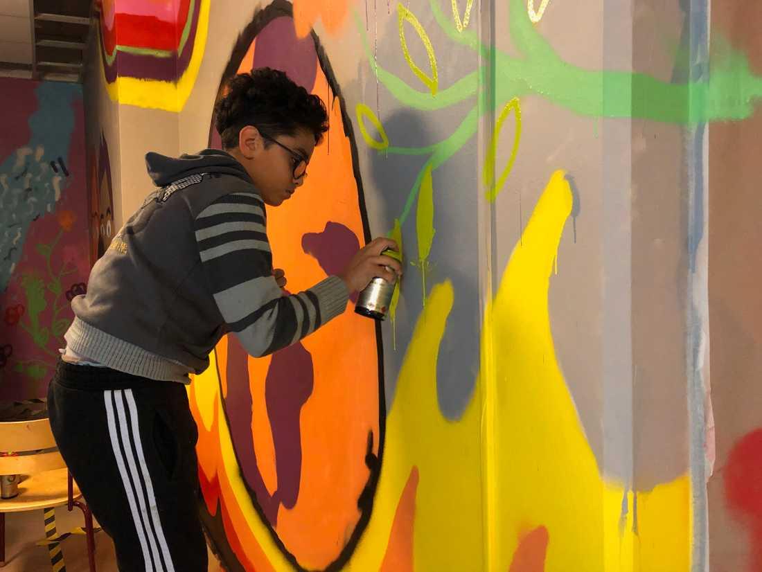 Mohammed Refai sprayar noggrant på gul färg på muralmålningen.