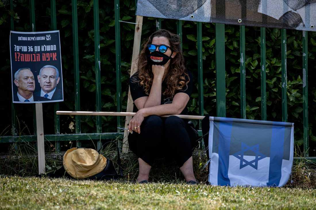 """En kvinna med ett munskydd med texten """"crime minister"""" har kommit för att titta på HD-förhandlingarna på storbildsskärm i närheten av domstolen i Jerusalem. Plakatet ifrågasätter det rimliga i en regering med rekordmånga 36 ministrar, vilket har krävts för att Netanyahu och Gantz ska blidka de partier i knesset som förlorar makt i och med regeringslösningen."""