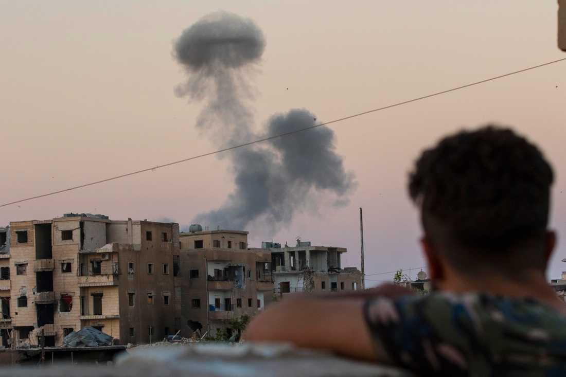 En MSF-soldat (Syriac Military Council), som stred tillsammans med SDF i Raqqa tittar mot en brinnande byggnad där IS-terrorister ska ha huserat.