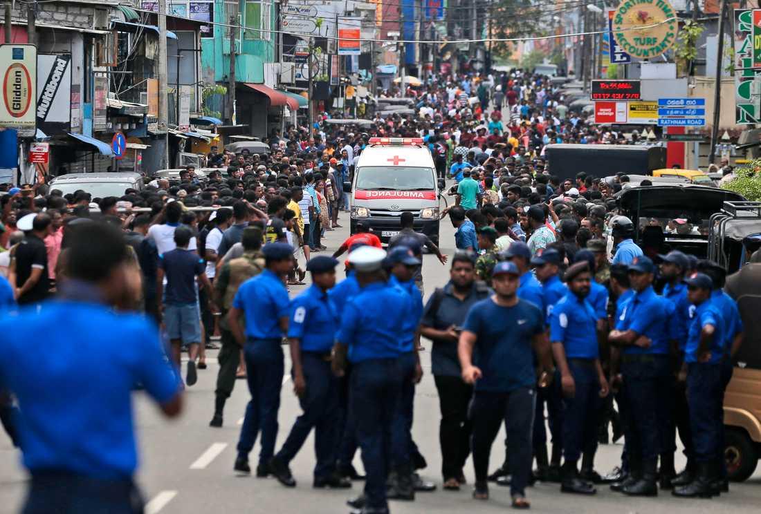 Ambulans åker genom folkhav i Colombo.