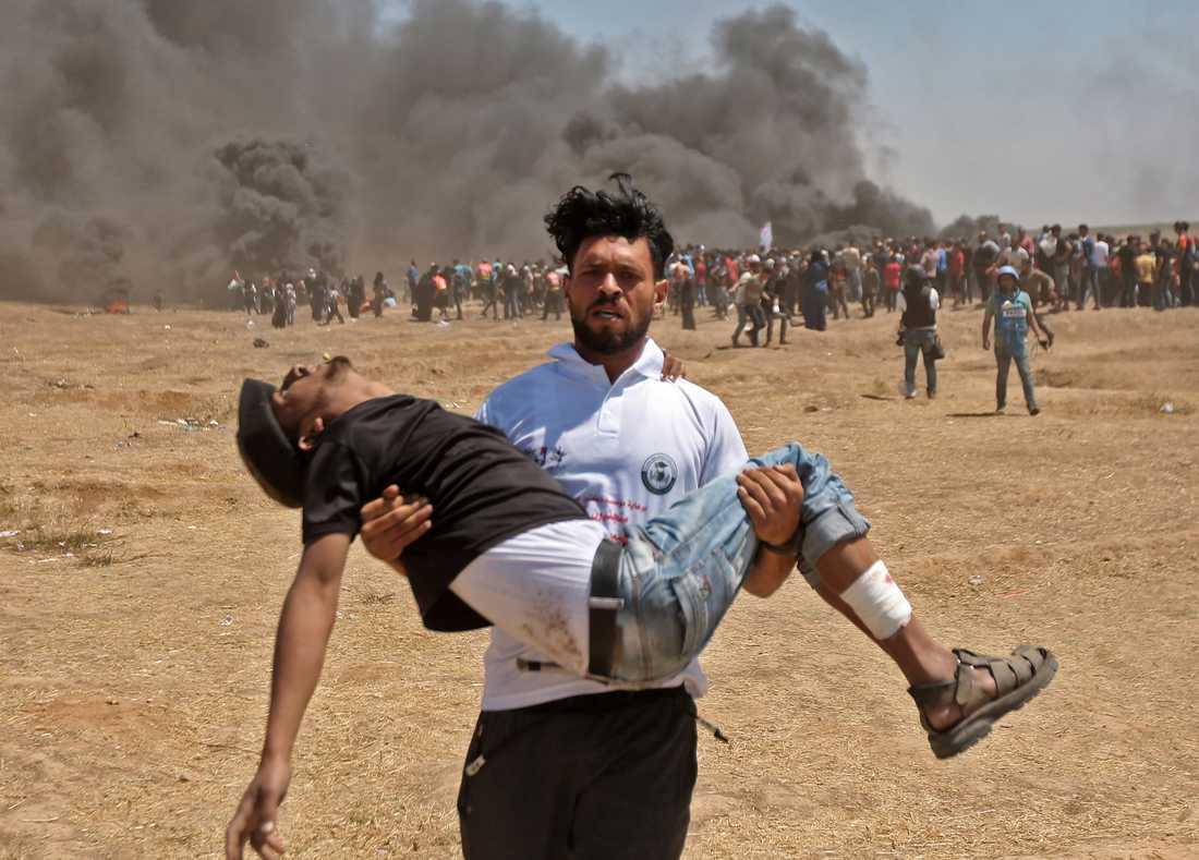 En palestinsk man bär en sårad demonstrant efter sammandrabbningar med israelisk militär vid Gazaremsan.