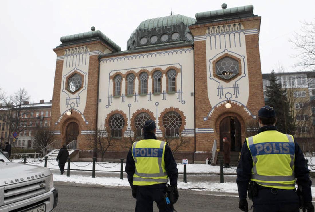 Polisen bevakar judiska församlingens minnesstund i synagogan i Malmö i samband med Förintelsens minnesdag 2013.