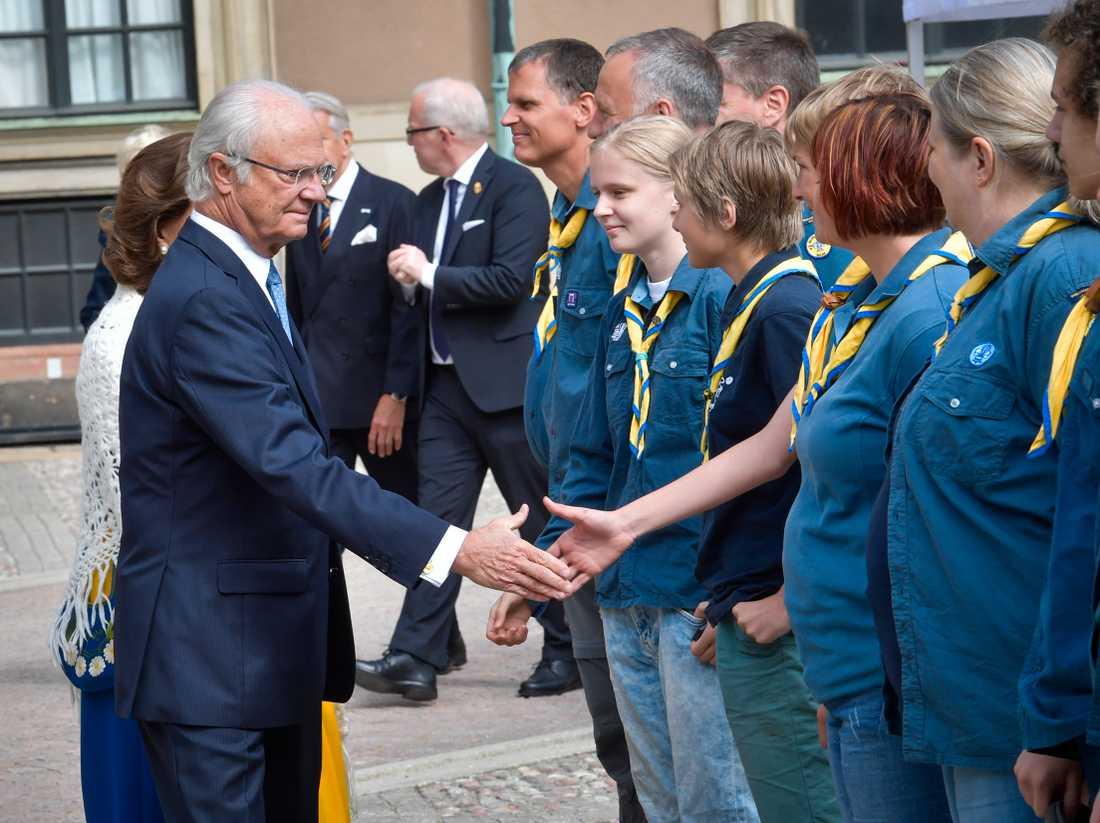 Kung Carl Gustaf och drottning Silvia hälsar på medlemmar ur Bergshamra scoutkår, under nationaldagsfirandet på Stockholms slott.
