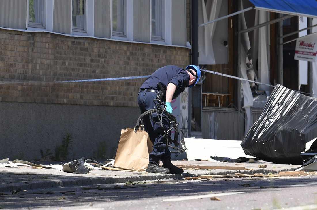 En av polisens tekniker ses bärandes på vad som ser ut som cykeldelar efter explosionen i Linköping.