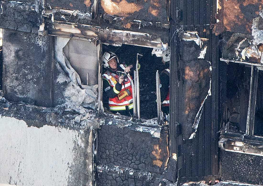 En av flera hundra brandmän inspekterar skadorna efter branden.