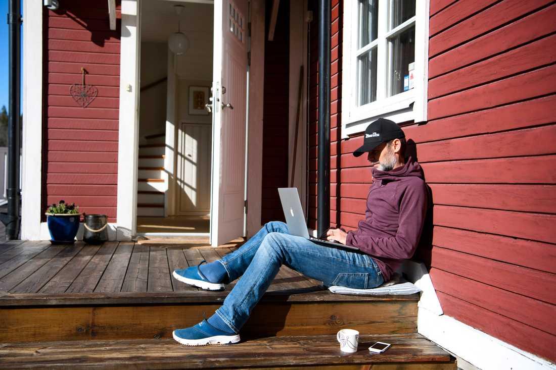 Man med bärbar dator jobbar hemifrån på sin altan. Arkivbild.