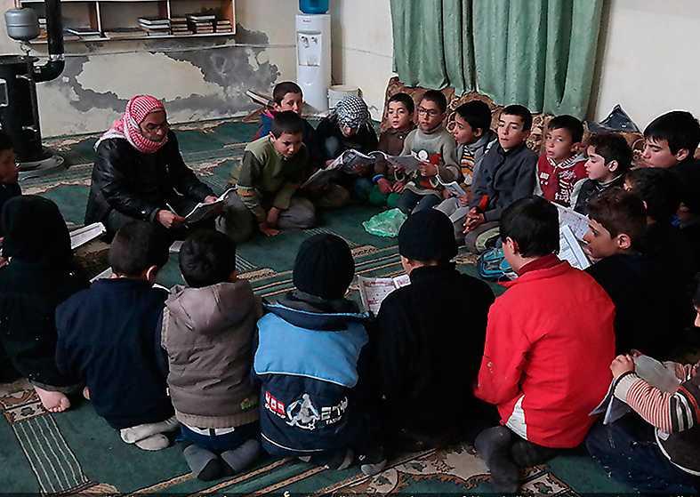 En IS-predikant lär syrianska pojkar i Tel Abyad att recitera koranen. Foto: AP