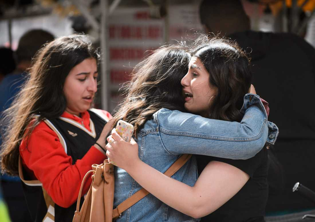 Vänner omfamnar varandra efter skottlossningen.