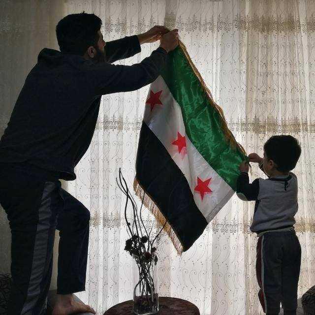 Monther Etaky hänger upp den syriska självständighetsflaggan i Aleppo 2016.