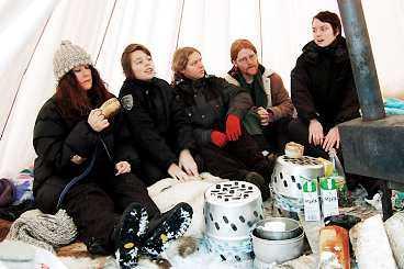 Zara Hallman och fältbiologer värmer sig i ett tält.