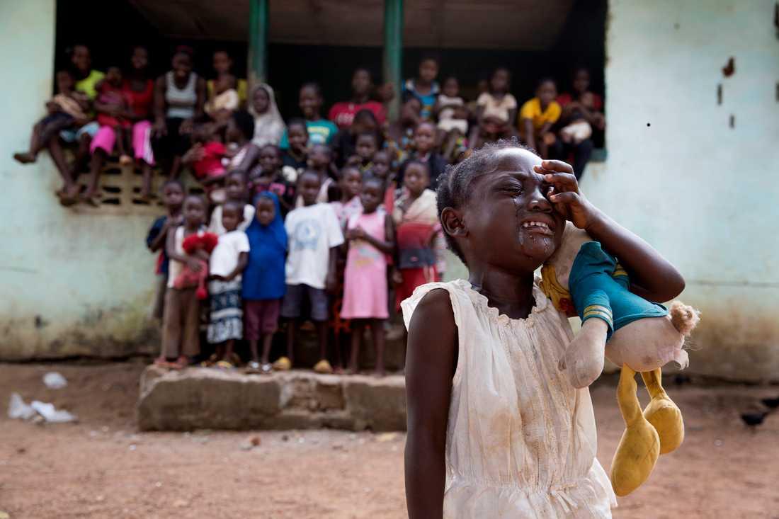 """I ett hus i en fattig by utanför Monrovia bor 46 föräldralösa barn. De har ingen mat, inte ens vatten. Femåriga Fatou håller hårt i sin smutsiga Kalle Anka. Barnen är lekfulla, men när Fatou ställer sig framför kameran brister det för henne. """" Mamma! Pappa!"""", skriker hon."""