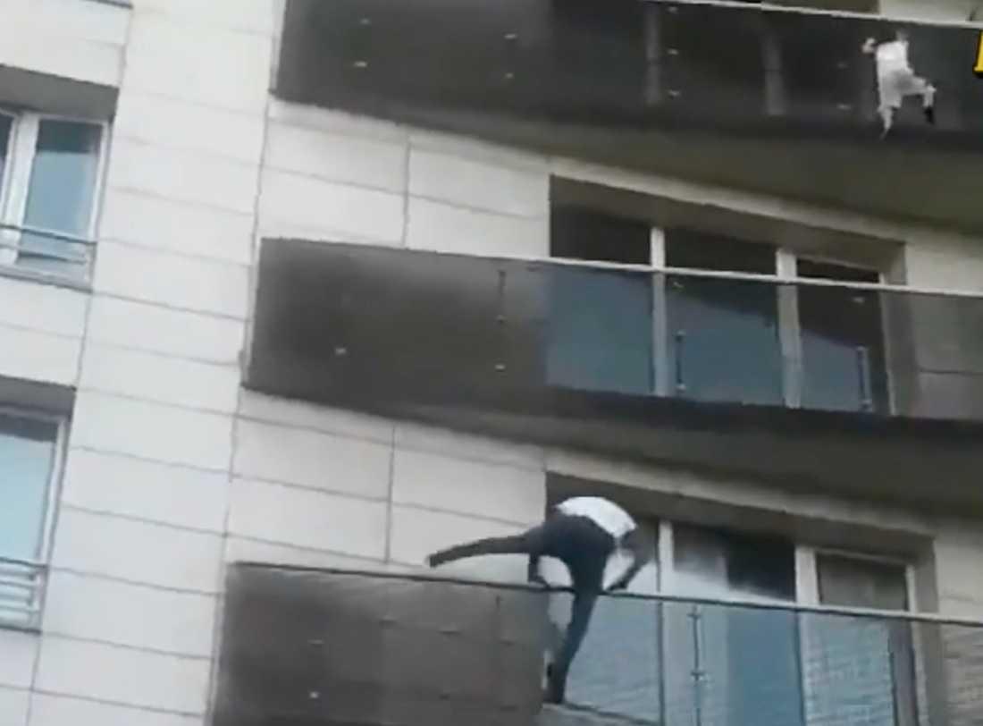 Mamoudou Gassama klättrar upp för att rädda barnet som hänger ut från balkongen.