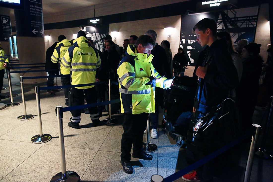 Kontrollanter fotar resenärers legitimationer med mobilkameror.
