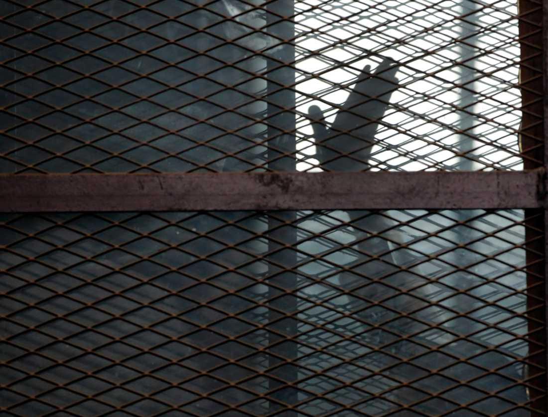 En medlem av Muslimska brödraskapet vinkar från försvarsfållan i en rättegång vid ett fängelse i Kairo. I höstas dömdes en stor grupp fångar till döden för att ha försökt fly från samma fängelse. Arkivbild.