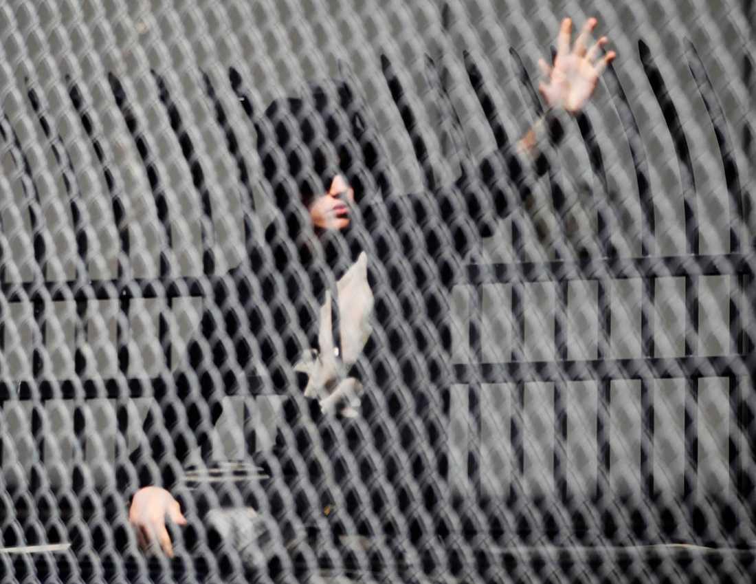 Justin Bieber vinkar till sina trogna fans som väntade på honom utanför polishuset.