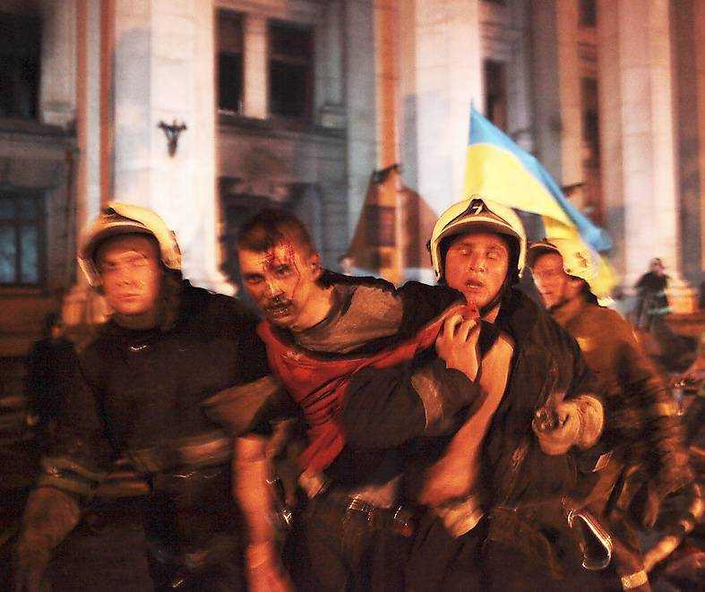 48 dödades  Brandmän räddar en skadad man i Odessa den 2 maj förra året. Efter mordbranden har jakten på oppositionella fortsatt och president Porosjenko ska till och med ha hyllat händelserna som en seger över separatister. Foto: AP