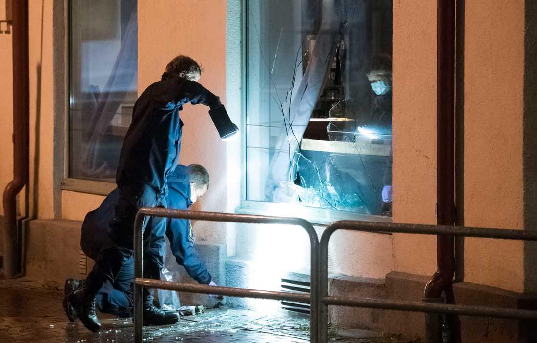 Polisens kriminaltekniker arbetar vid den krossade rutan till nattklubben i centrala Ängelholm efter nattens attentat.