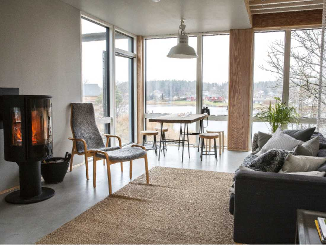 Vardagsrummet med fönster från golv till tak och utgång till terrass i västerläge. Kaminen  från Contura är husets hjärta, bredvid den en laminofåtölj. Matbord och pallar i kork från Ikea.