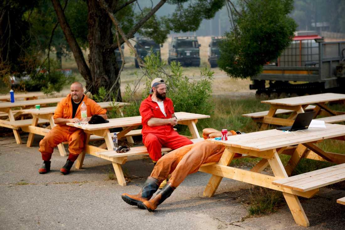 Utmattade brandmän tar rast i släckningsarbetet vid uppsamlingsplatsen i Ängra utanför Färila.
