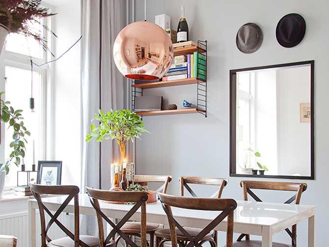Den kopparfärgade klotlampan sprider ett varmt sken över matbordet.