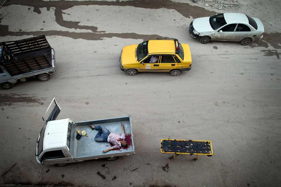 En död man har lastats på ett lastbilsflak utanför Dar al-Shifa-sjukhuset i Aleppo.