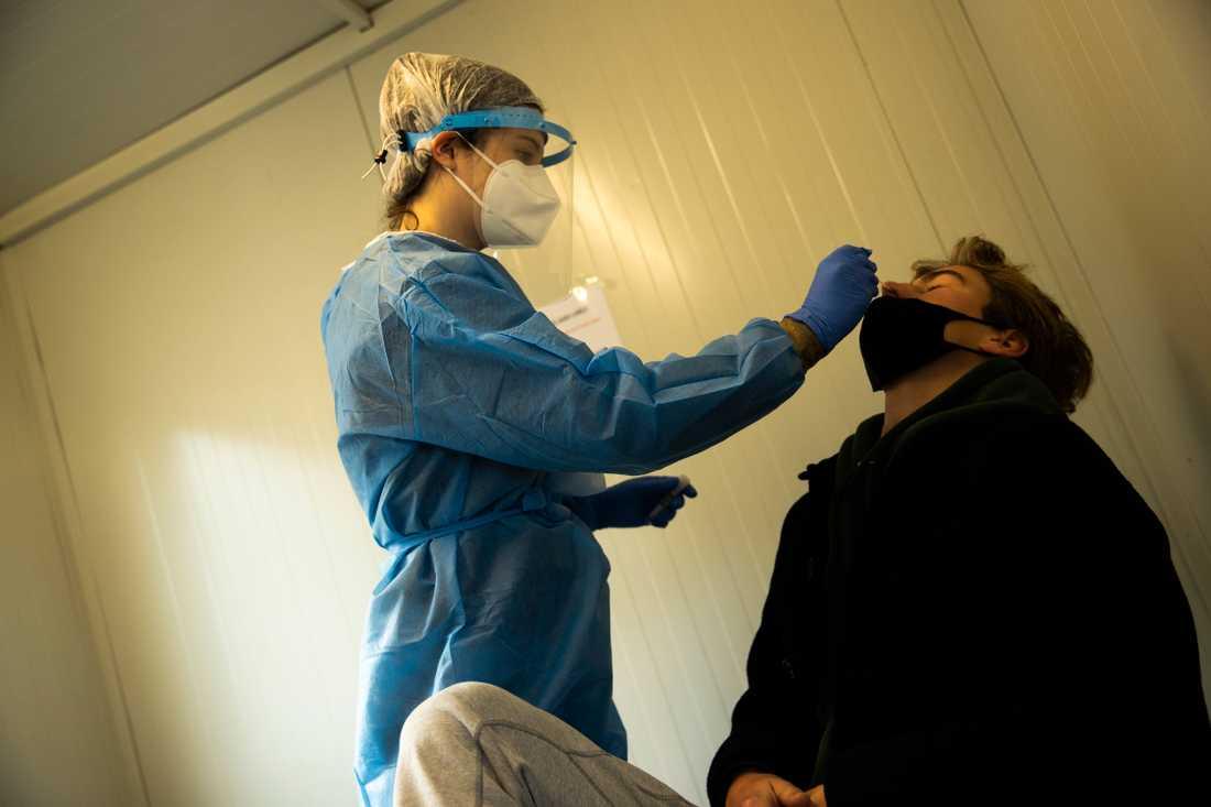 En sjukskötare coronatestar en resenär på Brysselflygplatsen Zaventem i Belgien.