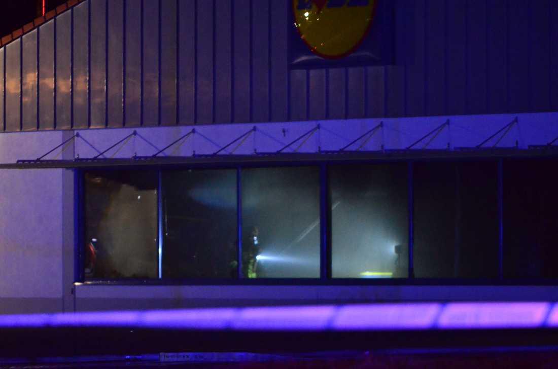 Rökdykare inne i butiken när elden släckts.