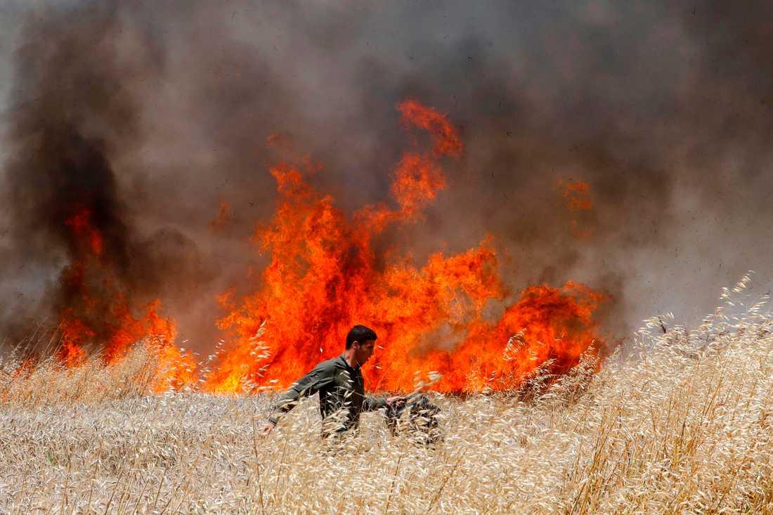 En israelisk soldat försöker släcka en eld på ett fält i närheten av gränsen mot Gazaremsan.