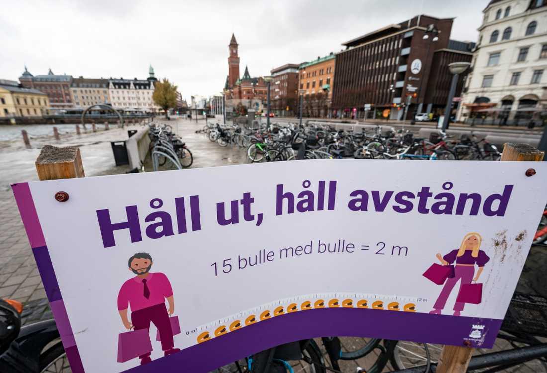 Helsingborgs stad mäter ut lämpligt socialt distanserat avstånd på 2 meter med hjälp ett lokalt bakverk på en skylt vid Knutpunkten under coronapandemin. Under vecka 48 konstaterades över 1 000 nya fall i Helsingborg.