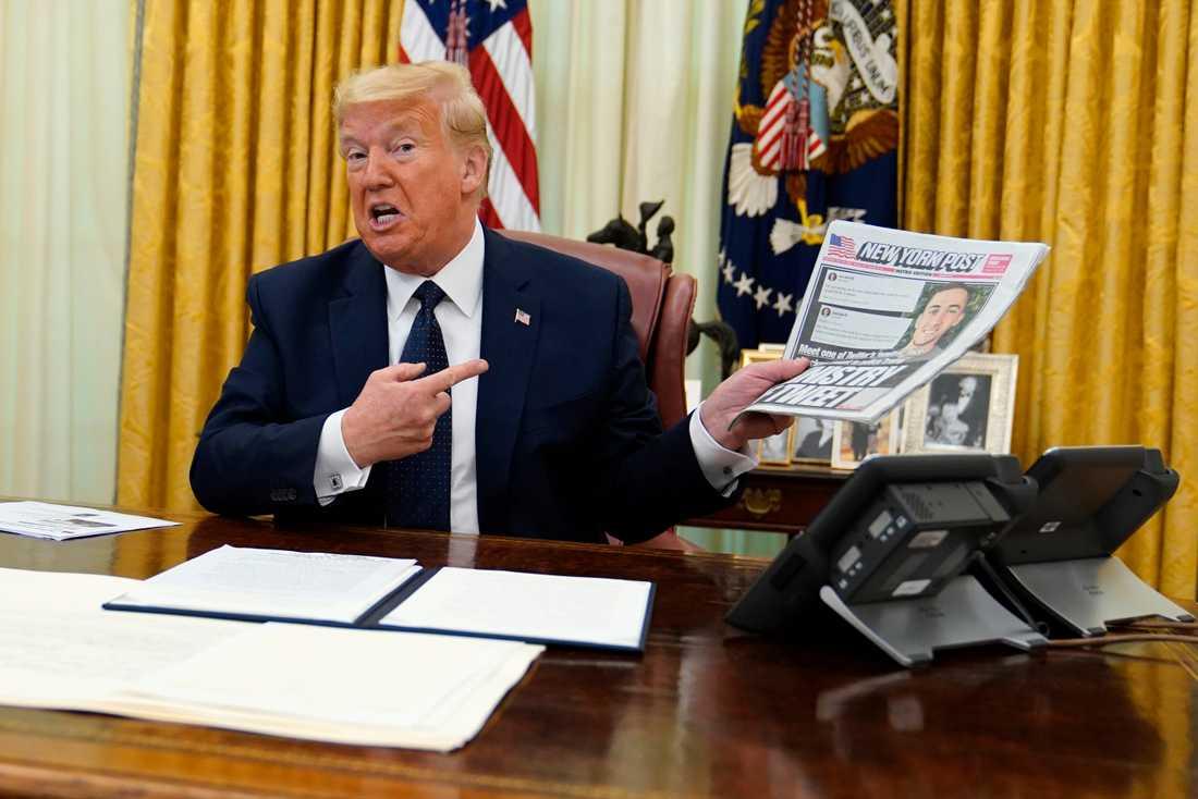 President Donald Trump precis innan han skriver på ordern som tar bort sociala mediers skydd mot rättsliga följder