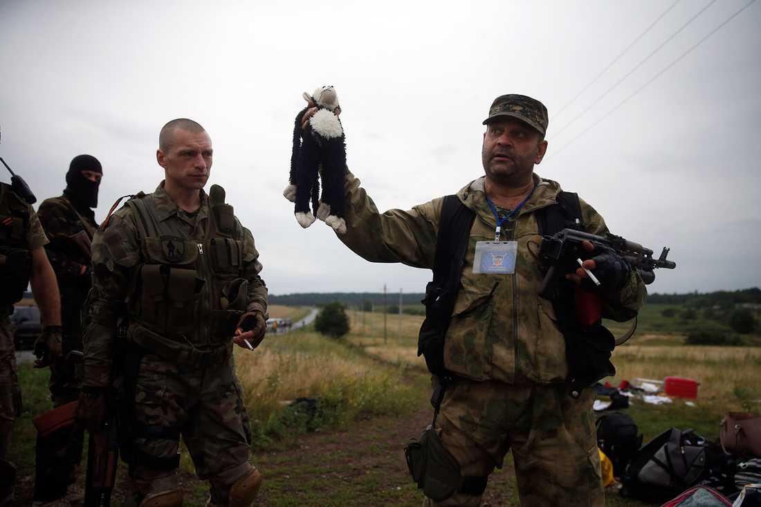 En prorysk separatist vid vrakplatsen. I handen håller han en nalle som hittades bland offrens ägodelar.