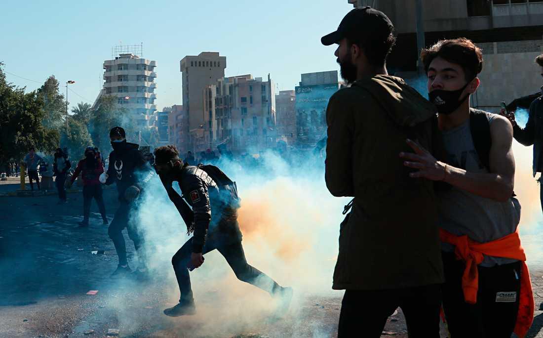 Regeringskritiska demonstranter flyr undan säkerhetsstyrkornas tårgas vid protester i Bagdad på söndagen.