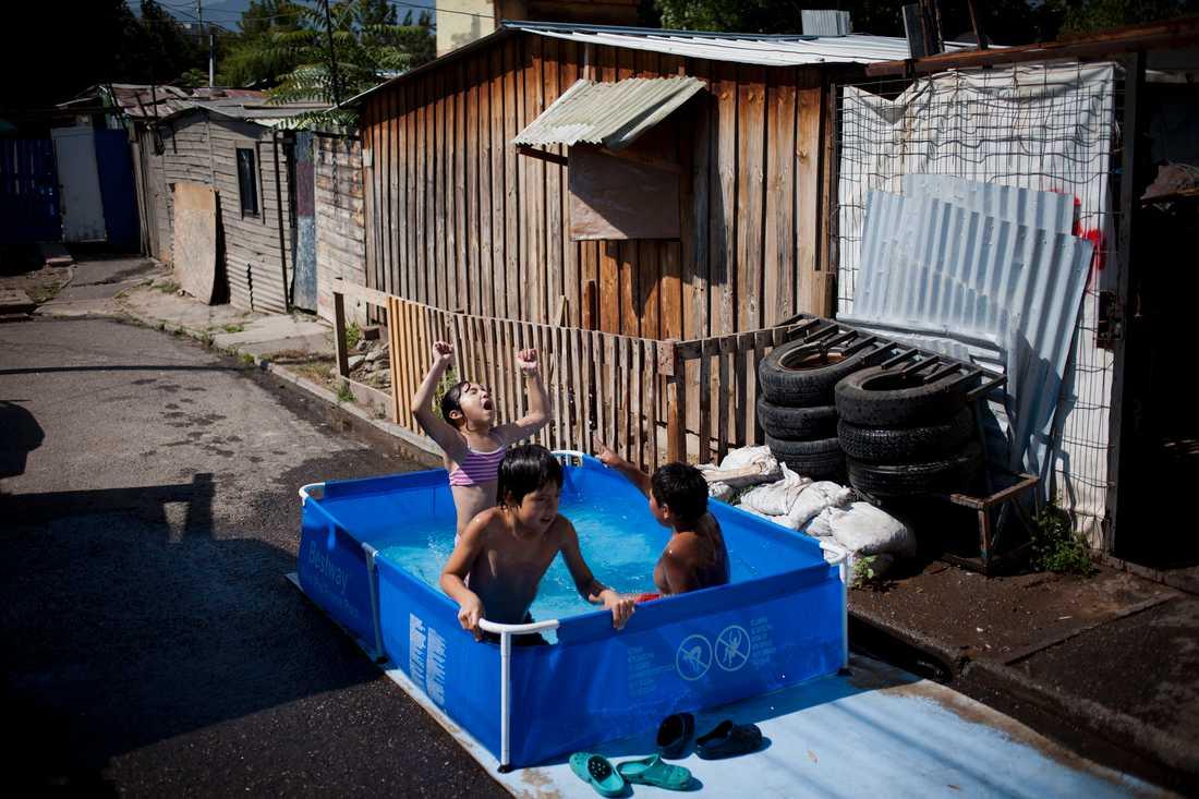 Barn badar i en liten pool i en gata i slumområdet Juan Pablo II i Santiago. Arkivbild.