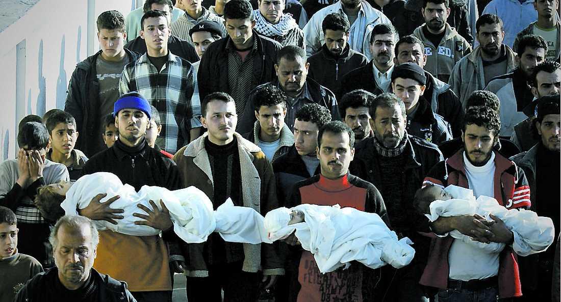 BEGRAVNINGSTÅG Släkten Samouni tågar mot det sista avskedet. Mohammeds, Ahmeds och Motasens kroppar – insvepta i vita skynken – ska begravas i Gaza City.