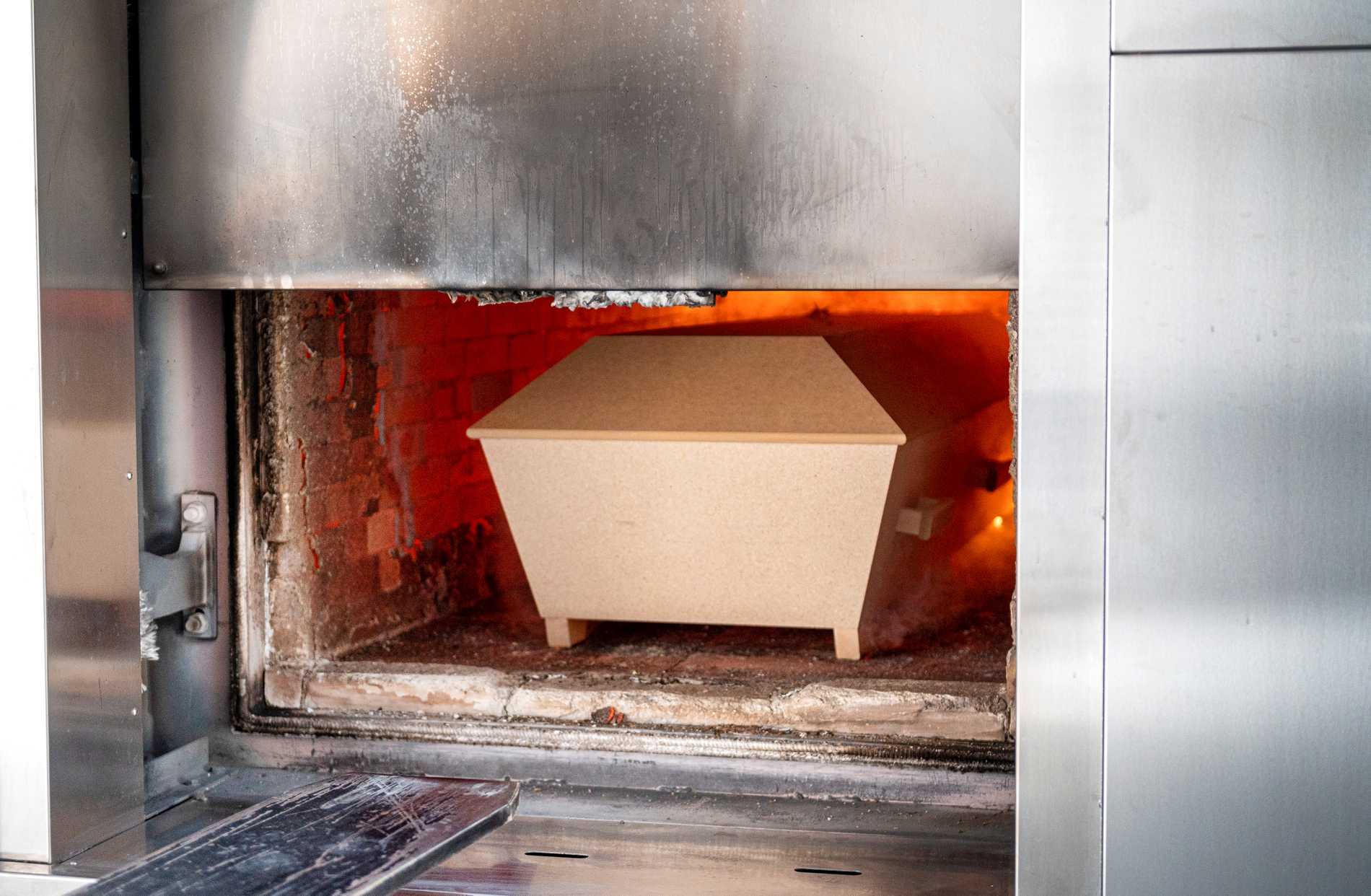 En kista förs in och bränns i ugnen, vid krematoriet på Skogskyrkogården i Stockholm.
