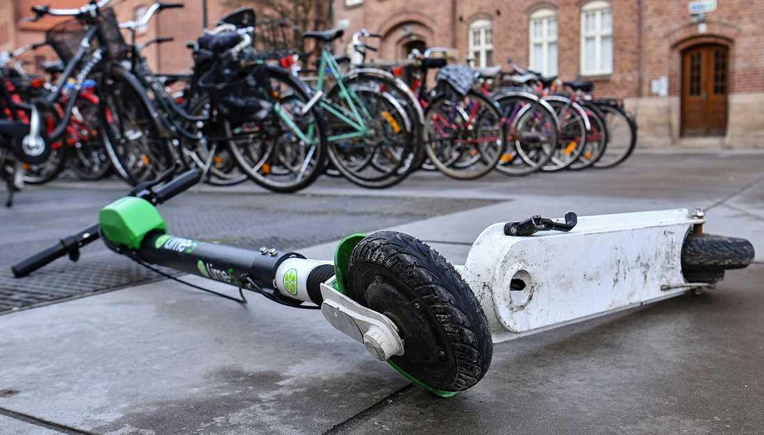 Elscooter liggande vid ett cykelställ utanför Triangeln i Malmö.
