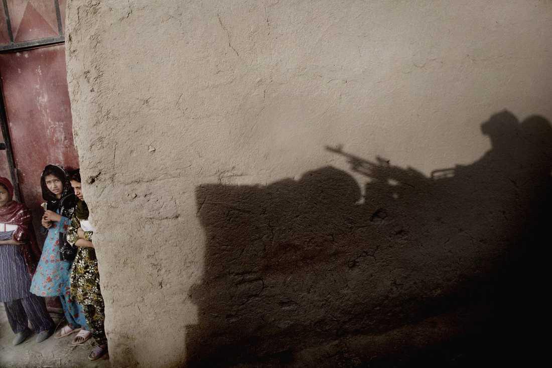 Rädda blickar när den svenska truppen passerar genom byn Alizayi.