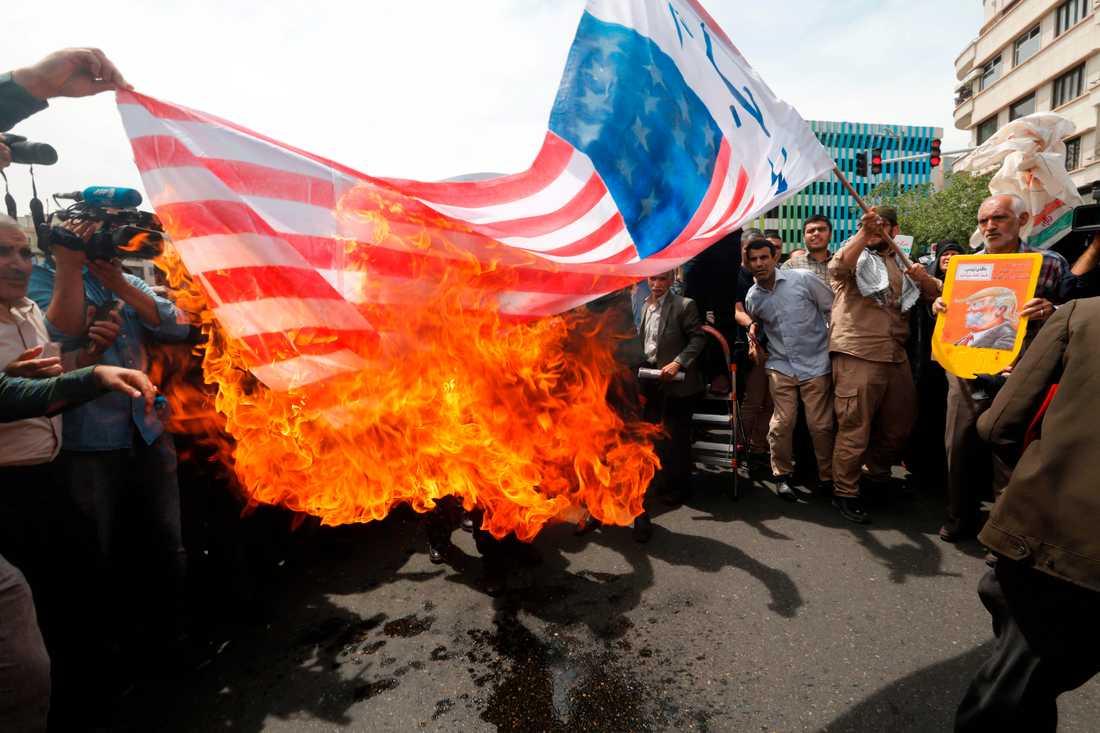 Demonstranter tänder eld på en amerikansk flagga i Irans huvudstad Teheran under fredagen.