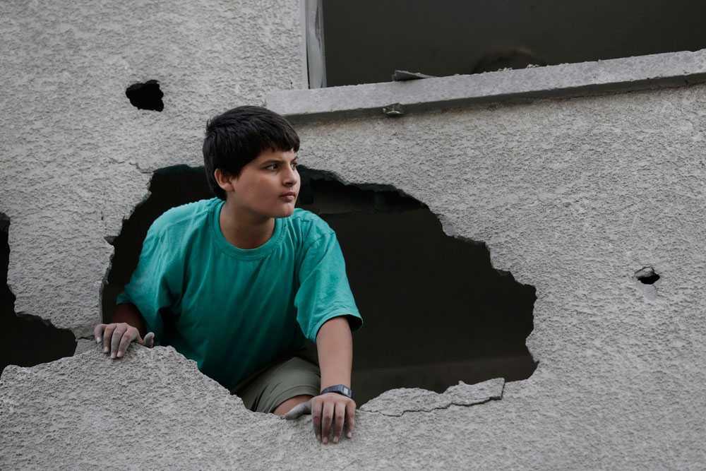 Under natten till 29 juli fortsätter raketer falla över Gaza. Israel slår till mot bland annat Hamasledaren Ismail Haniyehs hus, Hamas tv-station och Gazas enda kraftverk. Pojken på bilden tittar på tv-stationen från ett bostadshus som också skadades. Antalet dödsoffer på den palestinska sidan överstiger nu 1 100.